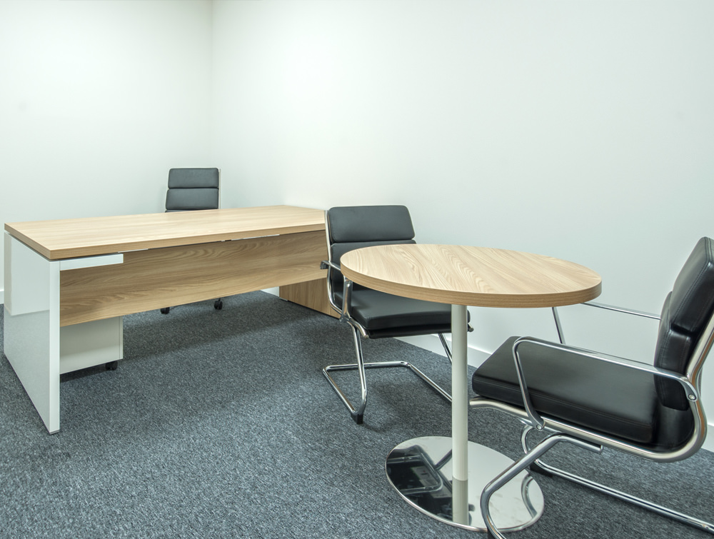 Straight office desk in wooden finish and round desk with black chairs