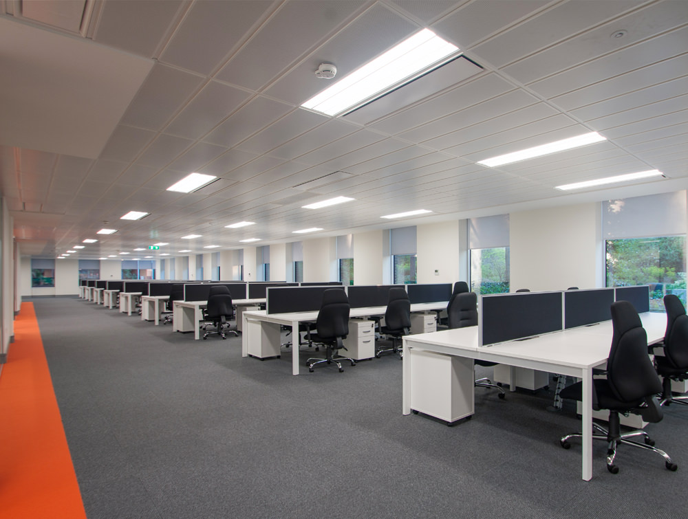 Apex call centre open floor. White Desks and black chairs