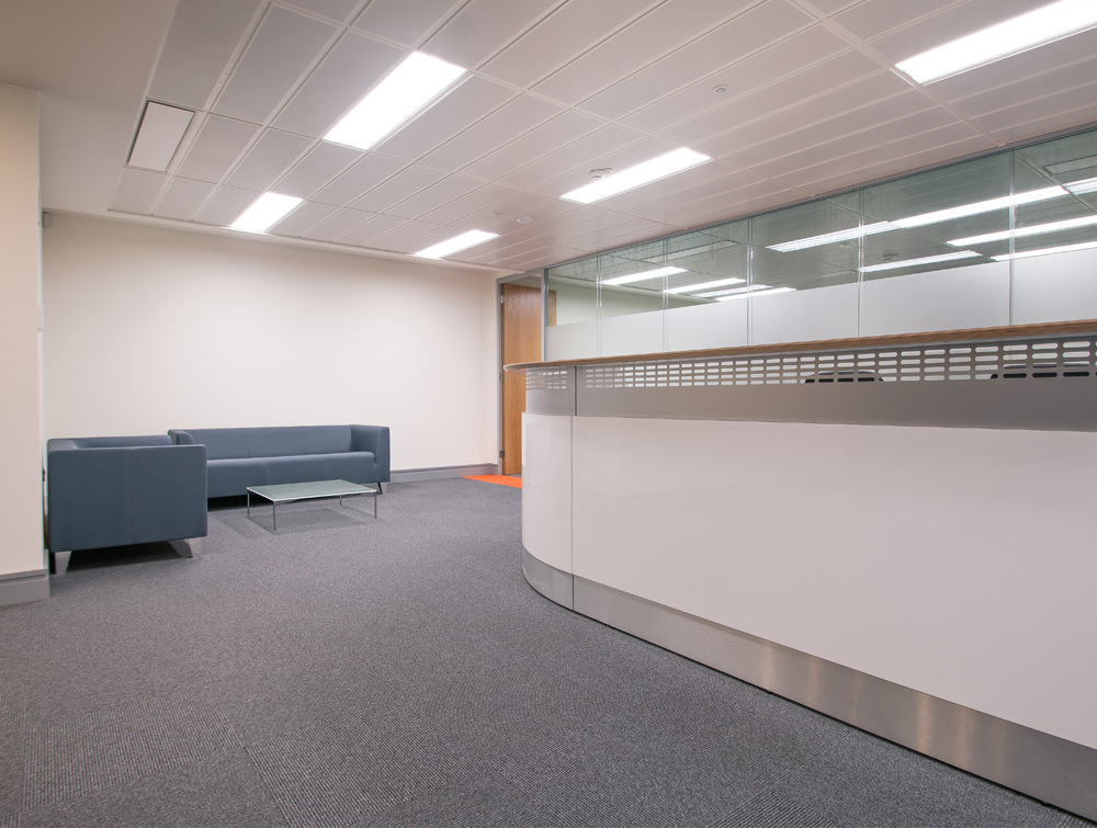 Apex Office Layout White Reception Desk with Grey Sofas and Glass Table