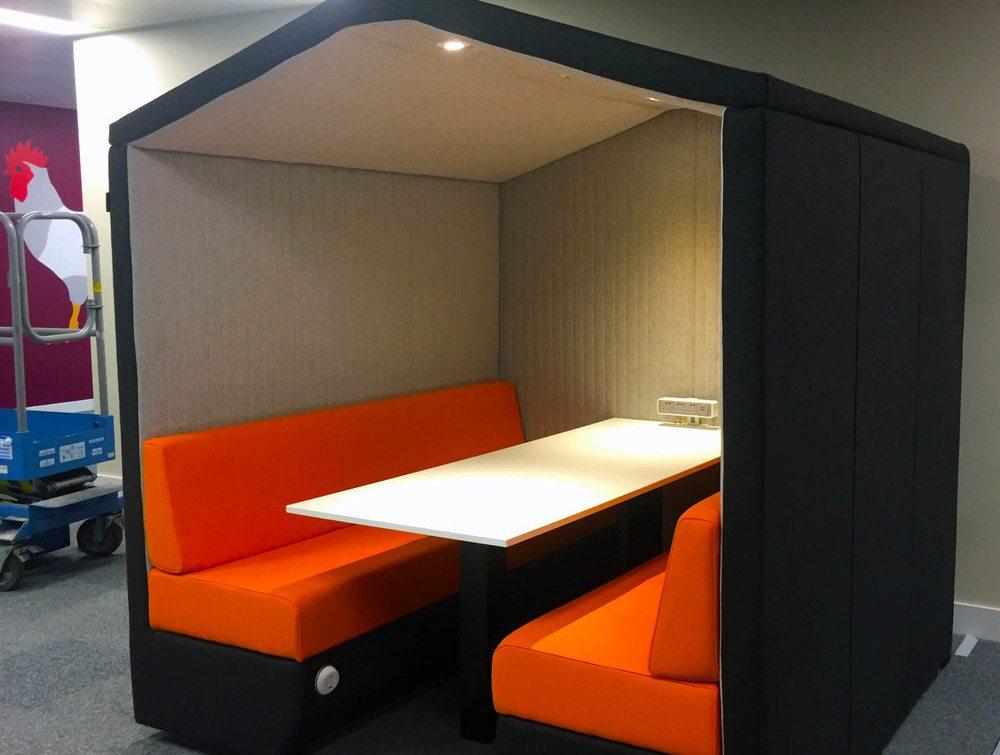 Bea 6 seater meeting pod with orange cushion and overhead LED light