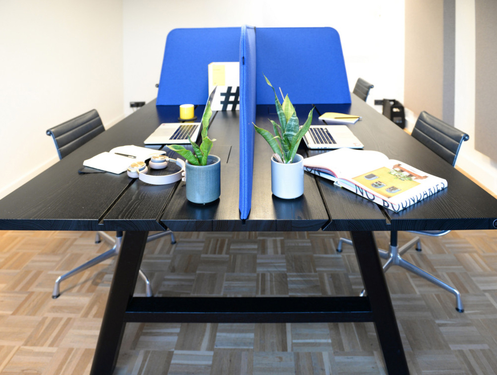 BuzziSpace-Desk-Cross-Acoustic-TableTop-Screen-Blue-on-Black-Table-with-Meeting-Room-Chair