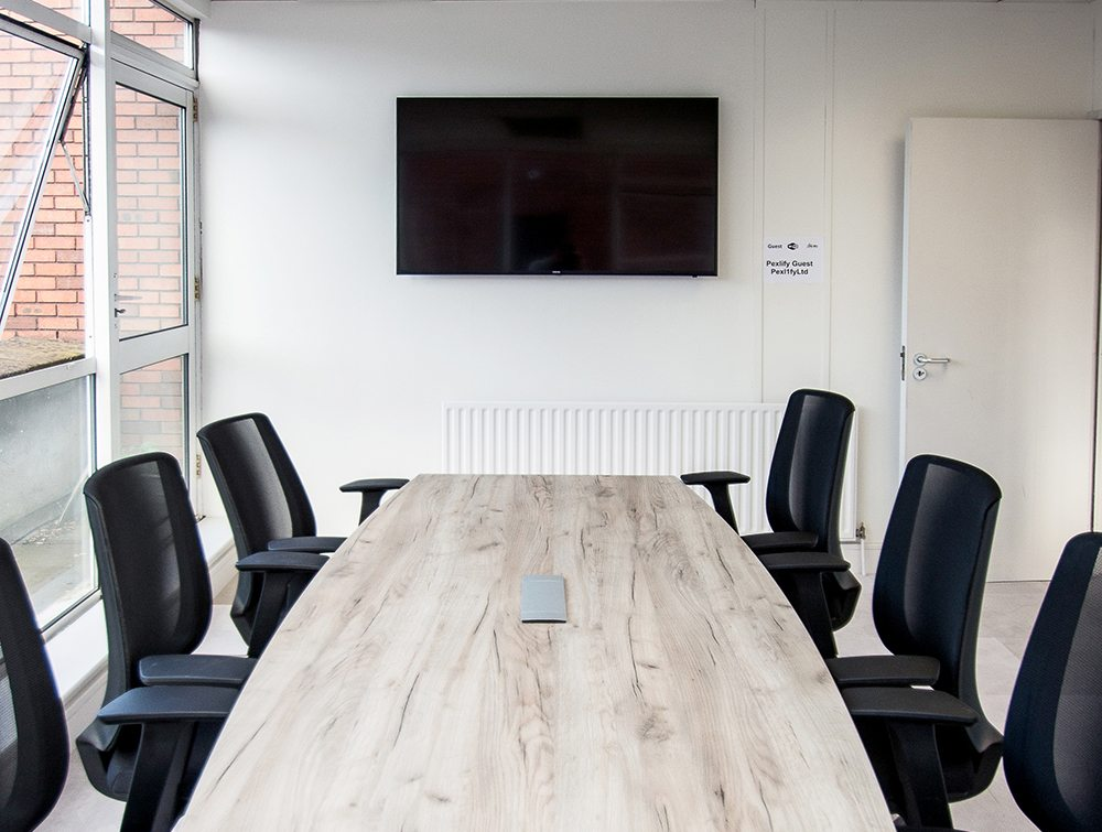 Confererence Table with Mesh Chairs in Front of Wall Mounted TV Screen