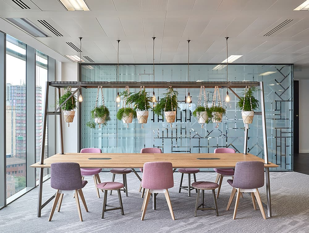 Relic-Cloud-Outdoor-Themed-Meeting-Room-Table-with-White-Frame-and-Natural-Table-Finish-and-Hanging-Plants.jpg
