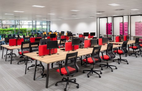 Social-Talent-Office-Layout-Beech-Back-to-Back-Desks-with-Red-Desk-Screens-and-Red-Mesh-Ergonomic-Chairs-
