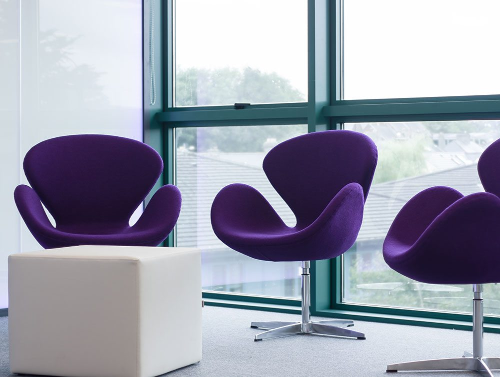 3 purple chairs in a meeting room office