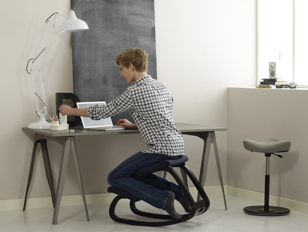 Varier Balans Kneeling Chair in black with a user