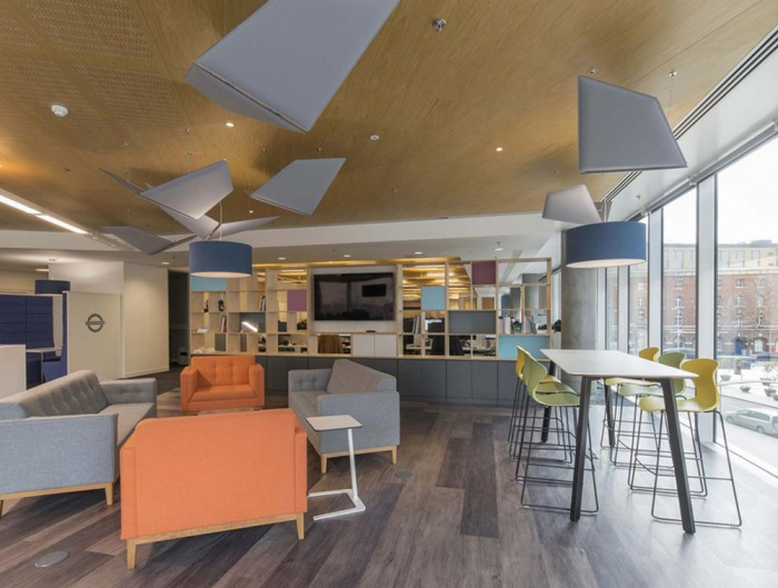 Wooden-Partitions-Grid-Between-Office-Space-and-Communal-Space-with-Sofas-High-Stool-Table-and-Acoustic-Ceiling-Panel-