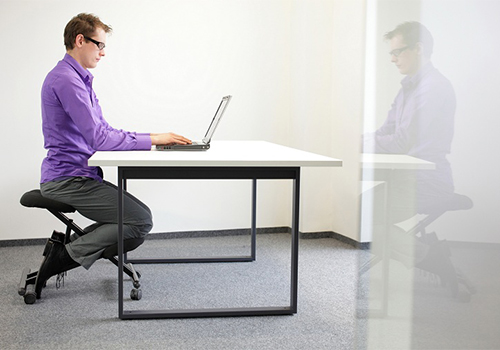 Man Using a Kneeling Chair in Office