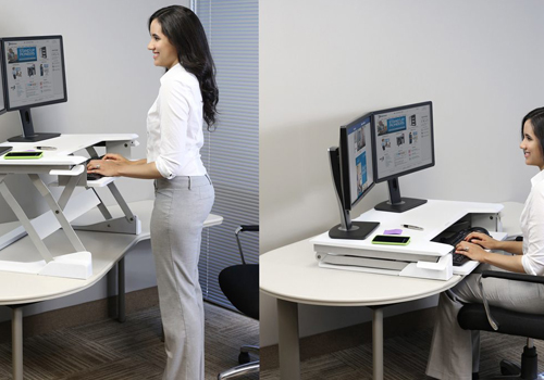 woman using a sit stand desk converter
