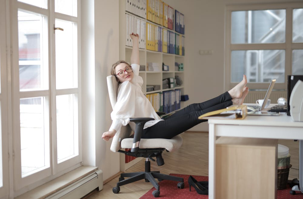 Woman Using Ergonomic Kneeling Chair in Office