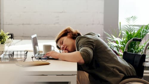 Woman sleeping on desk while working from home