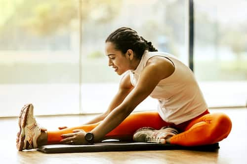 Woman stretching on yoga mat before walk