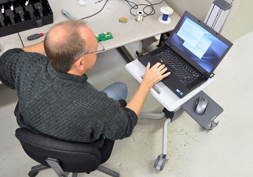 Man Using Laptop Cart at Work
